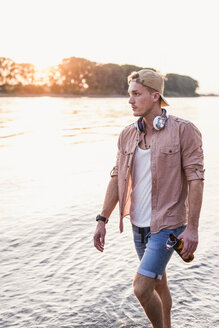 Young man walking at the riverbank at sunset - UUF11555