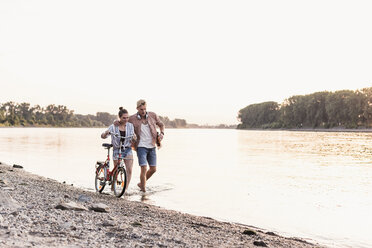 Young couple with bicycle wading in river - UUF11558