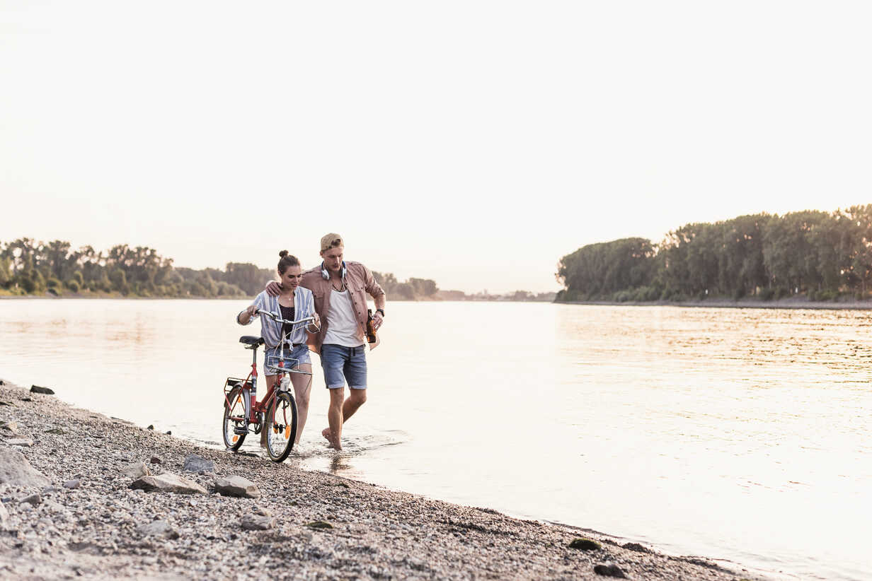 Young couple with bicycle wading in river - UUF11558 - Uwe Umstätter/Westend61
