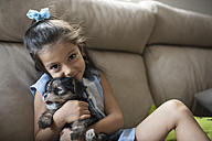 Portrait of smiling little girl sitting on the couch with her puppy - JASF01797