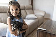 Portrait of smiling little girl with her puppy at home - JASF01800