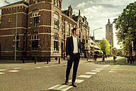 Netherlands, Venlo, businessman walking on a street - KNSF02402