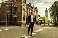 Netherlands, Venlo, businessman walking on a street - KNSF02402