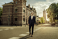 Netherlands, Venlo, businessman walking on a street with plastic bag over his head - KNSF02405
