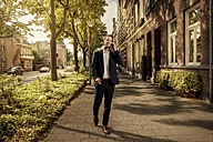 Netherlands, Venlo, businessman on cell phone walking on pavement - KNSF02411