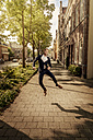 Netherlands, Venlo, happy businessman jumping on pavement - KNSF02414