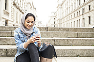 UK, England, London, young woman wearing hijab using cell phone in the city - IGGF00119