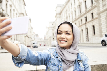 UK, England, London, young woman wearing hijab taking a selfie in the city - IGGF00122