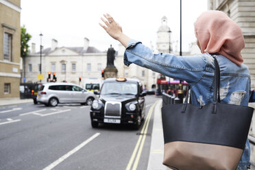 UK, England, London, young woman wearing hijab hailing a taxi - IGGF00128