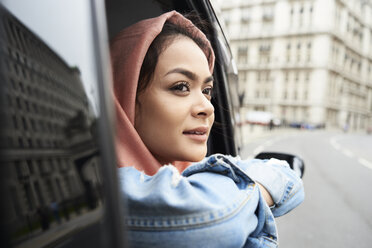 UK, England, London, young woman wearing hijab looking out of a taxi - IGGF00131