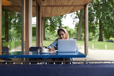 Young woman wearing hijab studying with her laptop on a terrace of a cafe - IGGF00134