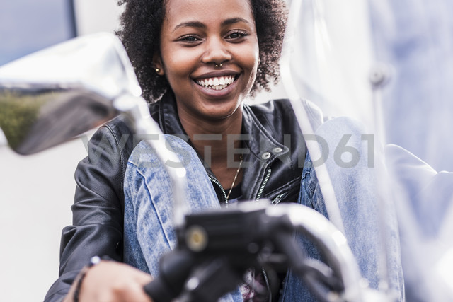 Portrait of smiling young woman with her motorcycle - UUF11567