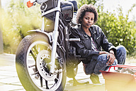 Portrait of young woman with her motorcycle - UUF11573