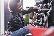 Young woman maintaining her motorcycle - UUF11576