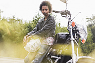 Portrait of young woman with her motorcycle - UUF11579