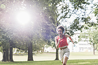 Young woman with headphones running in park - UUF11582