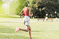 Young woman with headphones running in park - UUF11585