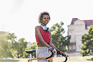 Smiling sporty young woman with bicycle in park - UUF11594