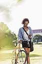 Young woman with cell phone pushing bicycle in park - UUF11600