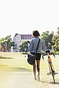 Young woman with cell phone pushing bicycle in park - UUF11603