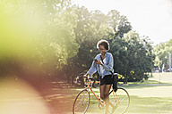 Young woman with cell phone pushing bicycle in park - UUF11606