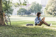 Young woman resting in park using tablet - UUF11612