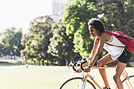 Smiling young woman riding bicycle in park - UUF11618