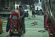 Worker with machine in factory - ZEF14524