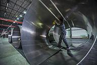 Worker examining metal in factory - ZEF14530