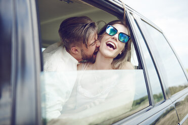 Playful affectionate young couple in car - ABIF00011