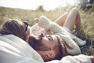 Happy young couple lying in grass - ABIF00020