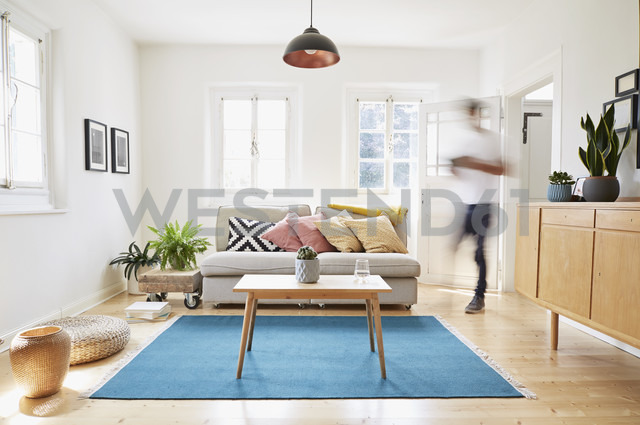Man walking in bright modern living room in an old country house - PDF01262 - Philipp Dimitri/Westend61