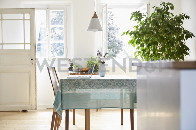 Laptop standing on dining table in an old country house - PDF01274 - Philipp Dimitri/Westend61