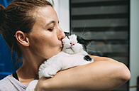 Woman holding and kissing her cat - GEMF01772