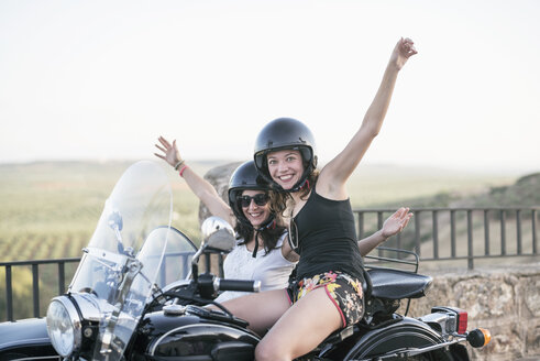 Portrait of two laughing women with their sidecar motorcycle - JASF01806