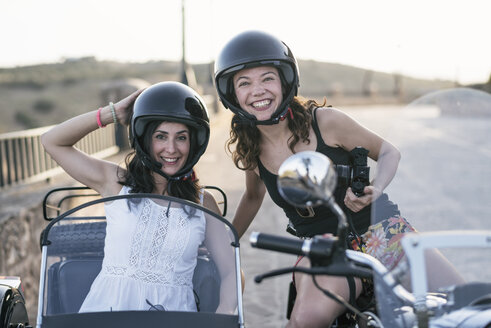 Portrait of two laughing women with their sidecar motorcycle - JASF01809