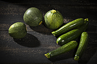 Eight ball squashes and courgettes on dark wood - MAEF12395