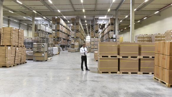 Businessman with laptop standing in warehouse - LYF00760