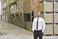 Portrait of confident businessman standing in warehouse - LYF00763