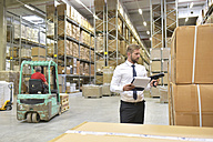 Businessman with clipboard in warehouse scanning goods - LYF00766