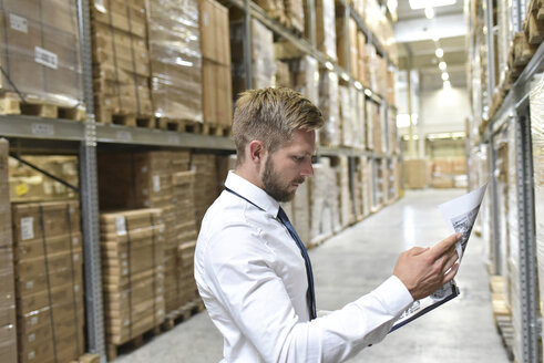Businessman looking at documents in warehouse - LYF00772