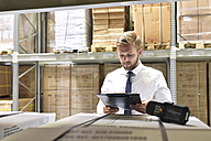 Businessman with clipboard and barcode scanner in warehouse - LYF00775