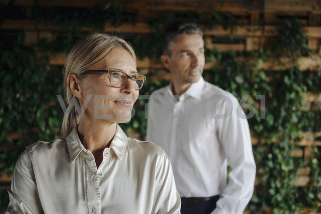 Businessman and businesswoman in green office thinking - JOSF01365