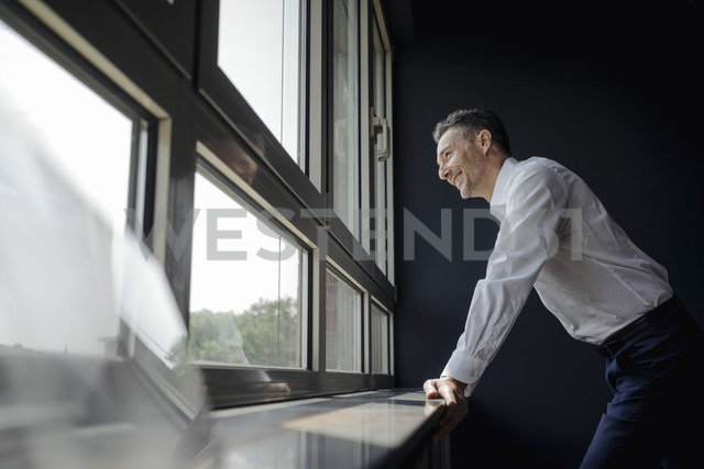 Smiling businessman in office looking out of window - JOSF01374 - Joseffson/Westend61