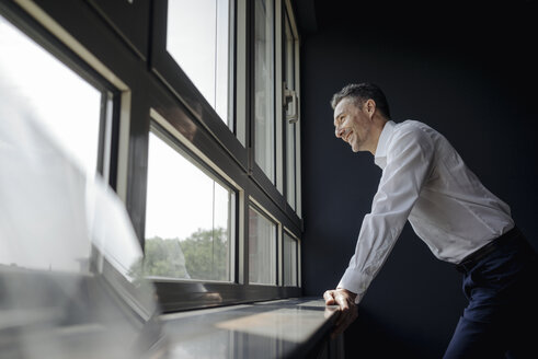 Smiling businessman in office looking out of window - JOSF01374