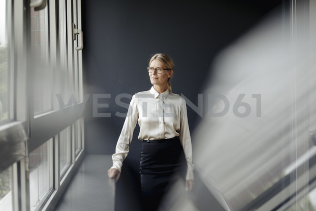 Businesswoman in office looking out of window - JOSF01377