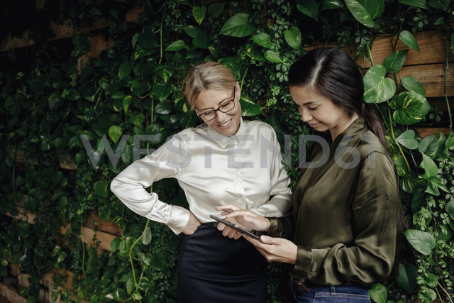 Two businesswomen in green office looking at tablet - JOSF01383 - Joseffson/Westend61