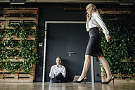 Businessman sitting and businesswoman on cell phone walking in green office - JOSF01386