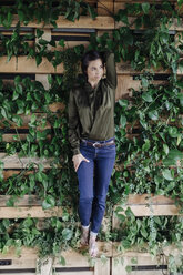 Young woman at wall with climbing plants - JOSF01404