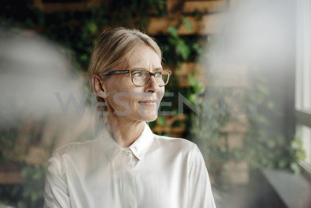 Businesswoman in green office looking out of window - JOSF01407